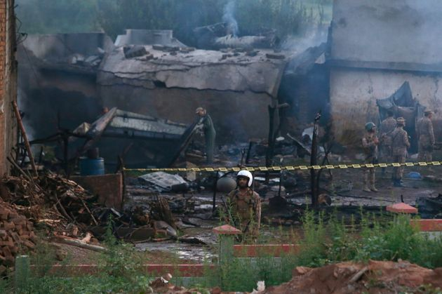 Pakistan army officials examine the site of a plane crash in Rawalpindi, Pakistan, July 30,