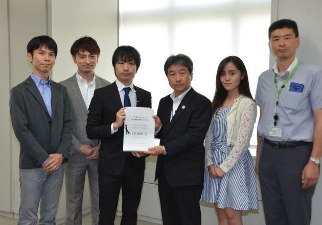 署名を渡したNPO法人フローレンス代表理事の駒崎弘樹さん(中央左)と、署名を受け取った東京都教育庁の佐藤聖一・高等学校教育指導課長(中央右)=東京都庁
