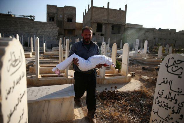 Un hombre lleva a enterrar el cuerpo de un niño, en un cementerio deDouma,