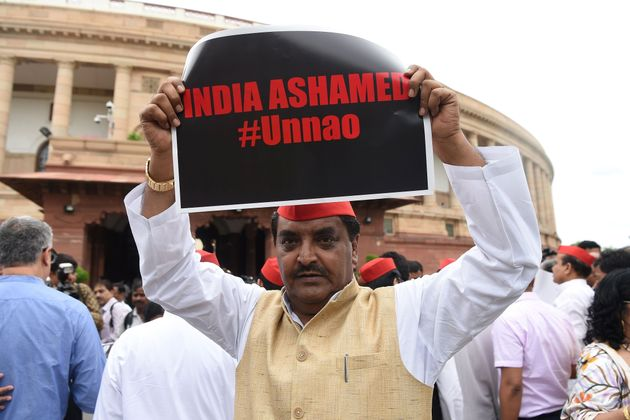 A member of the parliament of Samajwadi Party displays a placard during a protest calling for action...