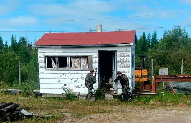 This RCMP photo shows officers searching for murder suspects in Gillam, Man., earlier this month. So...