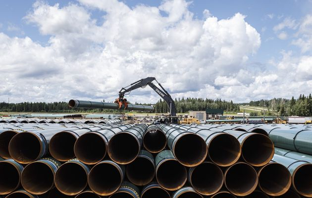 Pipe for the Trans Mountain pipeline is unloaded in Edson, Alta. on Tuesday June 18,