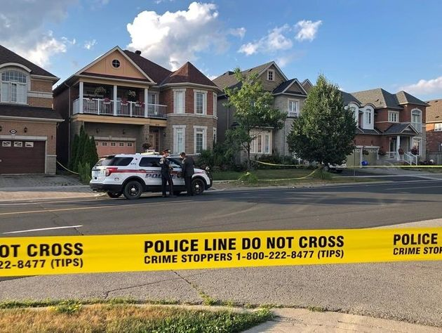York Regional police officers stand outside of a home in Markham, Ont. where four people were found dead...