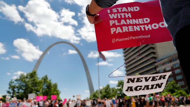 Abortion-rights supporters stand on both sides of a street near the Gateway Arch as they take part in a protest in favor of reproductive rights Thursday, May 30, 2019, in St. Louis. A St. Louis judge heard an hour of arguments Thursday on Planned Parenthood's request for a temporary restraining order that would prohibit the state from allowing the license for Missouri's only abortion clinic to lapse at midnight Friday. (AP Photo/Jeff Roberson)