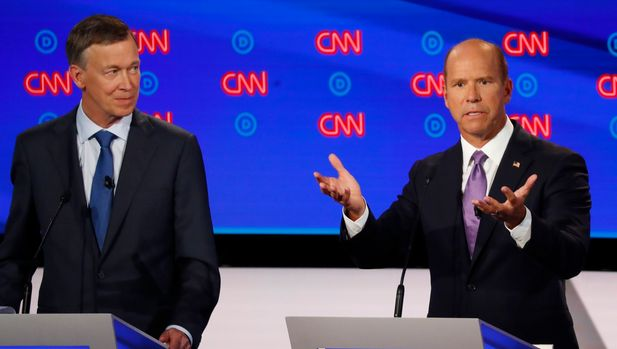 Former Colorado Gov. John Hickenlooper watches as former Maryland Rep. John Delaney speaks during the first of two Democratic presidential primary debates hosted by CNN Tuesday, July 30, 2019, in the Fox Theatre in Detroit. (AP Photo/Paul Sancya)