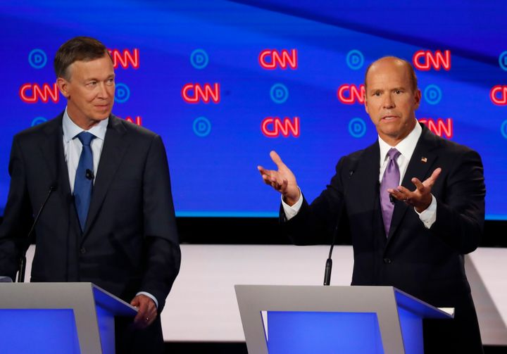 Former Colorado Gov. John Hickenlooper (left) looks on as fellow centrist John Delaney, a former Maryland congressman, speaks