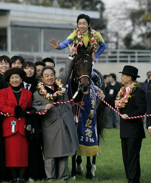 有馬記念を制した際のディープインパクトと武豊騎手(馬上)。Vサインする馬主の金子真人氏(千葉・中山競馬場、2006年12月24日)
