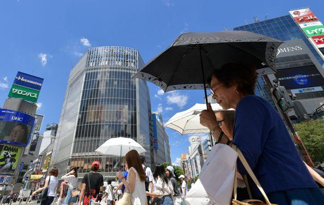 猛暑の中、日傘をさしながら街を歩く人々