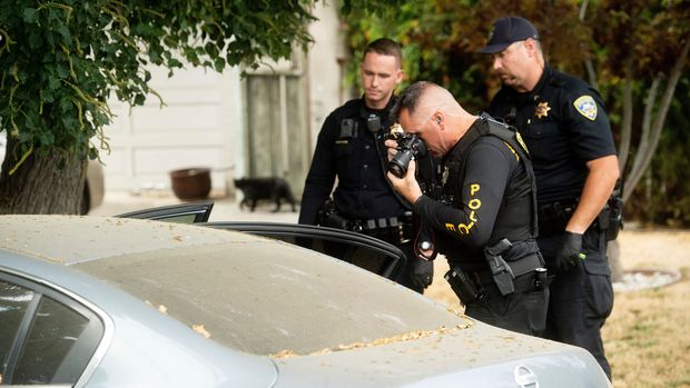 A police officer photographs a car outside the family home of Gilroy Garlic Festival gunman Santino William Legan on Monday, July, 29, 2019, in Gilroy, Calif. The Sunday evening shooting left at least three people, including a 6-year-old boy, dead and wounding about 15 others. (AP Photo/Noah Berger)