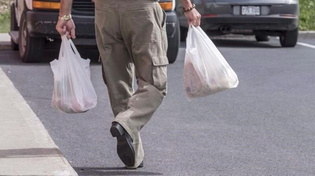 A man carries groceries in a plastic bag in