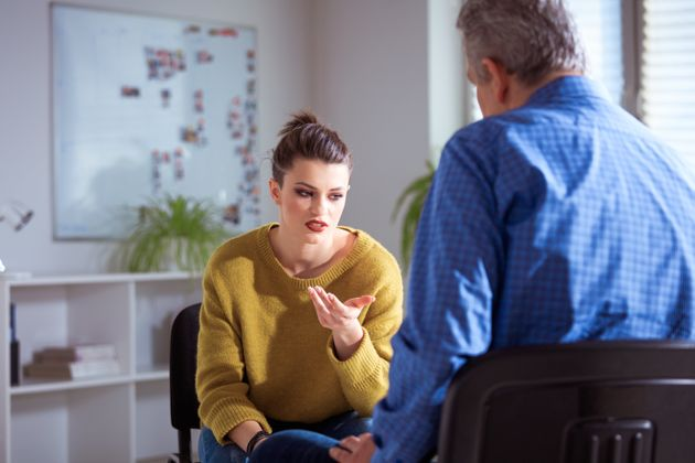 Sad university student gesturing while sharing problems to therapist. Mature mental health professional...