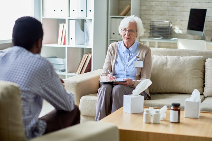 Serious senior female psychologist listening to patient and making notes for understanding problem in personal office