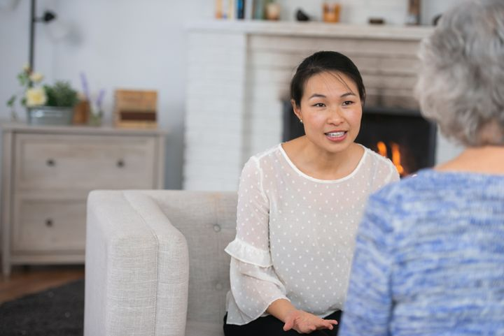 A woman of Asian descent smiles as she talks to her therapist. She is slightly smiling because she feels like she had a breakthrough.