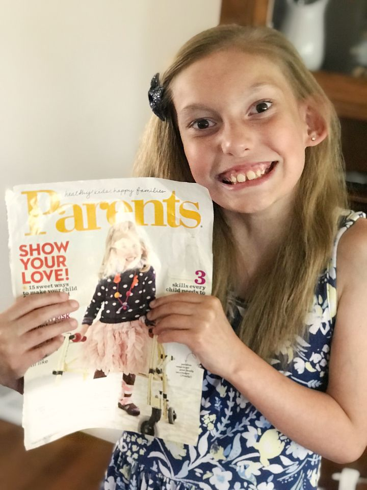 Evalyn in 2019, now 8 years old, holding the special magazine cover.