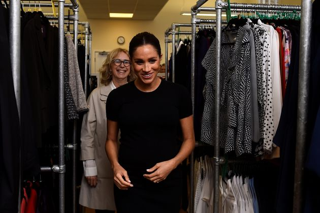 Meghan Markle and Lady Juliet Hughes-Hallett walk through racks of clothes during her visit to Smart...