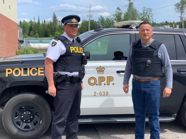 Ontario Minister of Indigenous Affairs Greg Rickford poses with a police officer in Kenora,