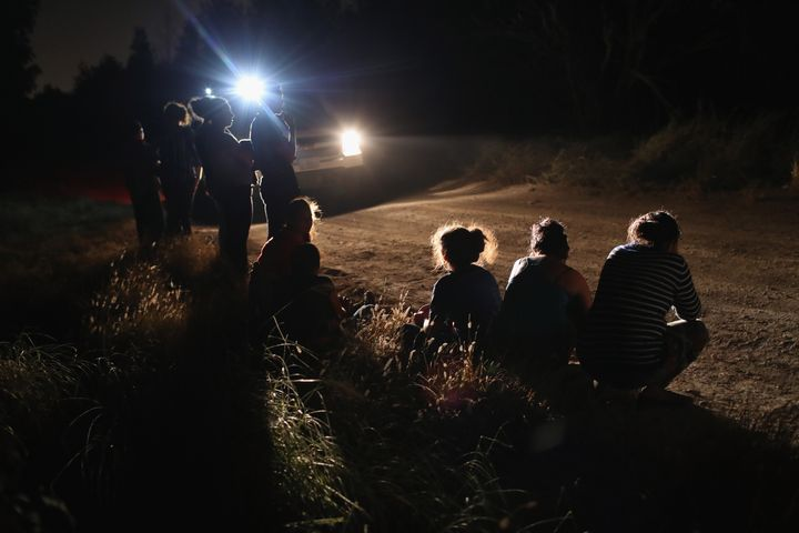 A U.S. Border Patrol vehicle illuminates a group of Central American asylum-seekers before taking them into custody near the