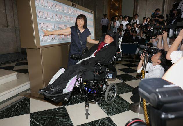 大型車いすで初登院する舩後靖彦参院議員(中央)=8月1日午前、国会内