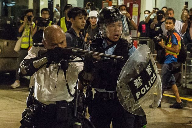 한 홍콩 경찰관이 콰이청 경찰서 인근에서 시위대를 향해 총을 겨누고 있다. 홍콩. 2019년