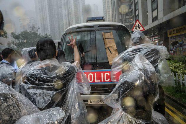 홍콩 동부법원 앞에 모인 시위대가 경찰 버스를 향해 폭력 진압을 규탄하고 있다. 홍콩. 2019년