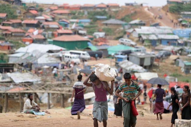 食料や住宅用資材を運ぶ難民たちが行き交う=2018年8月、バングラデシュ南東部コックスバザール、朝日新聞社撮影
