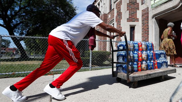 Teacher Cedric Cook pushes cases of water into Noble School in Detroit, Tuesday, Sept. 4, 2018. Some 50,000 Detroit public school students will start the school year Tuesday by drinking water from coolers, not fountains, after the discovery of elevated levels of lead or copper — the latest setback in a state already dealing with the consequences of contaminated tap water in Flint and other communities. (AP Photo/Paul Sancya)