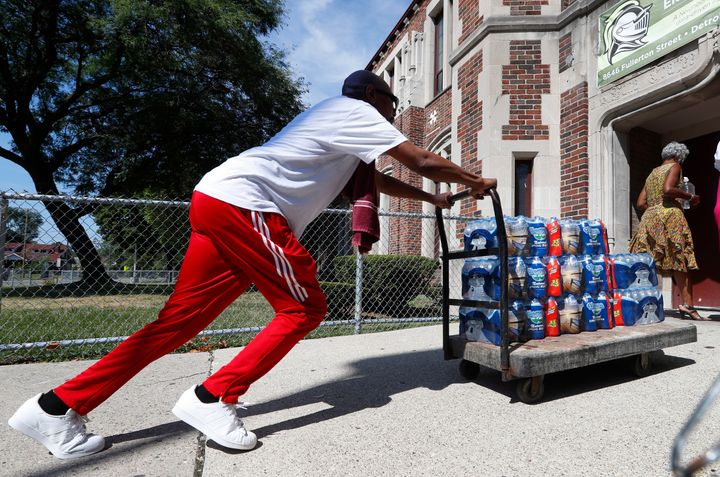 Teacher Cedric Cook pushes cases of water into Noble Elementary-Middle School in Detroit last year.