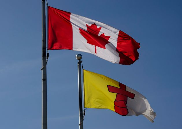 A Canadian flag flies beside the flag of Nunavut flag in Iqaluit on July 31,