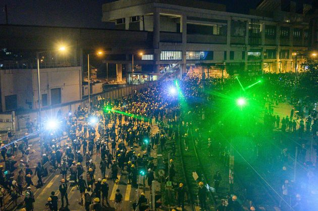 Protesters use laser lights as they move back to Yuen Long MTR station after a protest in Hong Kong on...