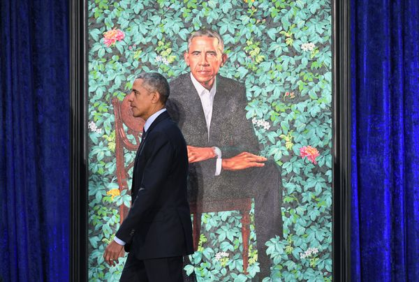 Obama walks by his presidential portrait at the Smithsonian National Portrait Gallery in Washington, DC.