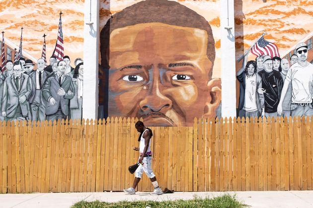 Un joven cruza ante el mural dedicado a Freddie Gray, muerto a golpes por la Policía de Baltimore...