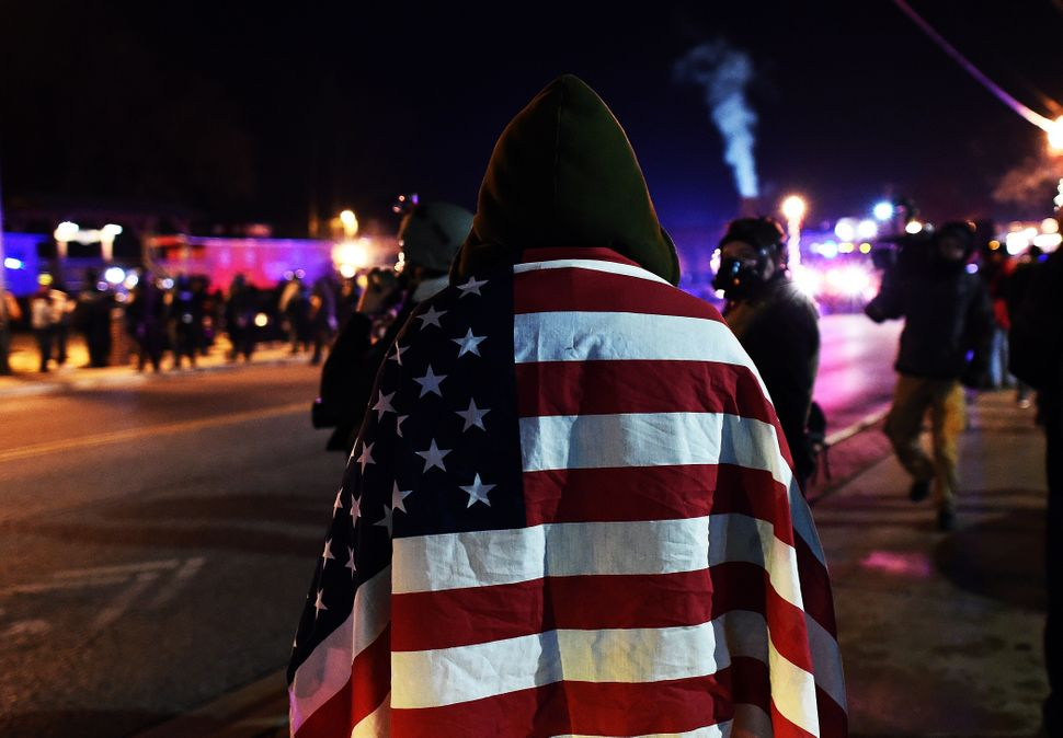 A protester wraps himself in a US flag in Ferguson, Missouri, on November 25, 2014 during demonstrations a day after violent protests and looting following the grand jury decision in the fatal shooting of a 18-year-old black teenager Michael Brown. Protest marches sprang up in cities across the US on November 25, amid a tense security operation in Ferguson, the Missouri town at the center of the country's latest racially-charged stand-off. Clashes erupted in the St Louis suburb for a second night, after grand jury's decision not to prosecute a white police officer for shooting dead an unarmed black teenager. AFP PHOTO/Jewel Samad        (Photo credit should read JEWEL SAMAD/AFP/Getty Images)