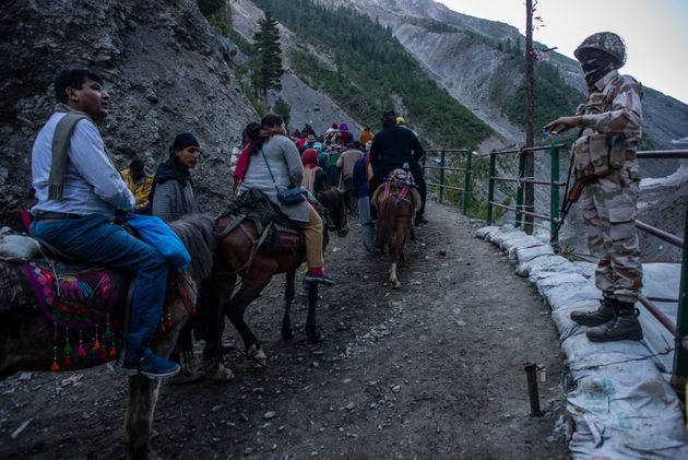 Government forces stand guard as people make their pilgrimage to the Amarnath shrine, on July 1, 2019,...