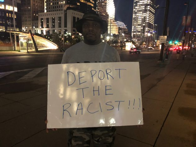 A 38-year-old protester named Brandon holds a sign near U.S. Bank Arena after a Trump rally in Cincinnati...