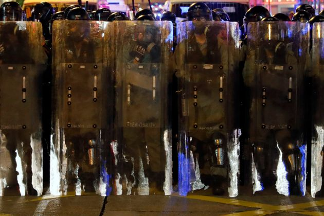 Riot police in protective gear form up during a confrontation with protesters in Hong Kong on