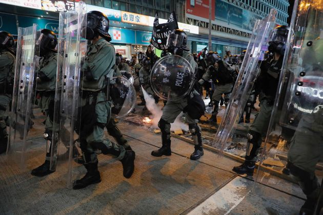 Riot police extinguish a fire set off by protesters in Hong Kong on