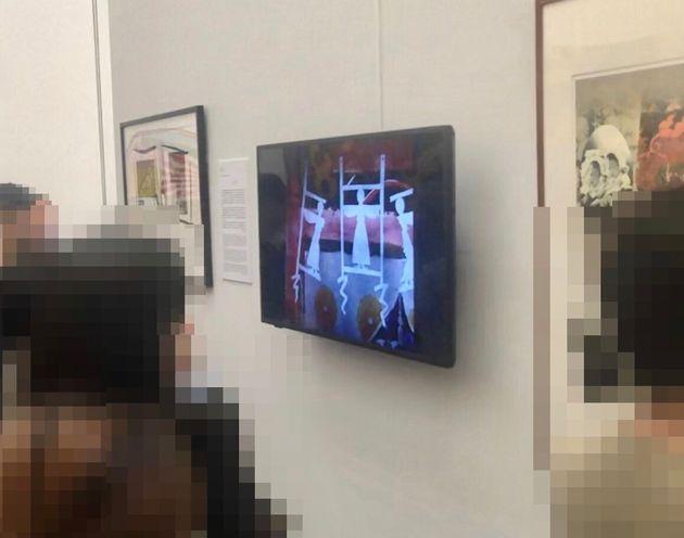 大浦氏の作品「遠近を抱えて」を鑑賞する人々。映像には「侮辱的だ」などとする批判が相次ぎ、抗議のうち4割は昭和天皇をモチーフにした作品に対するものだったという。(プライバシー保護のため、一部画像を加工しています)