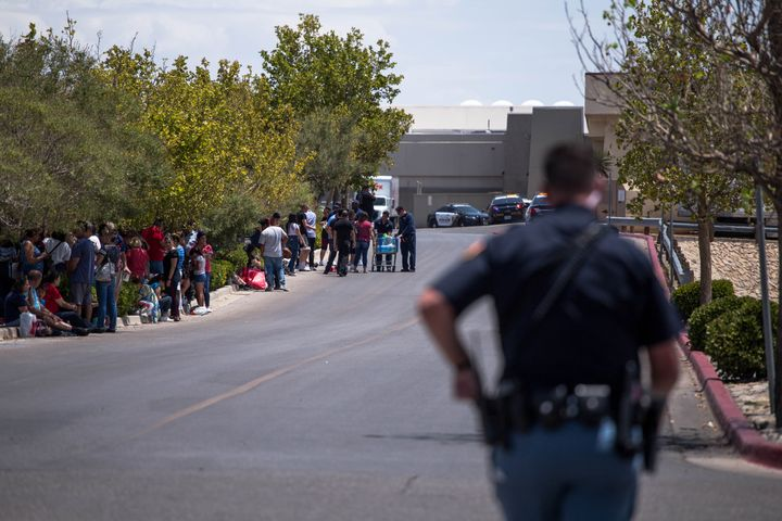 Evacuated people sit outside the Walmart in El Paso, Texas, on Saturday after the mass shooting that claimed at least 20 live