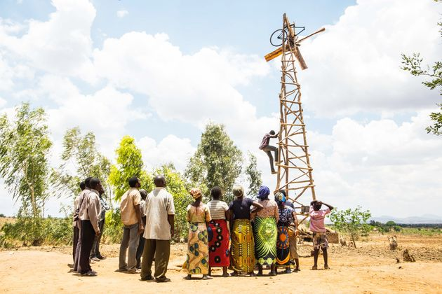 風車を見守る、家族と村人たち