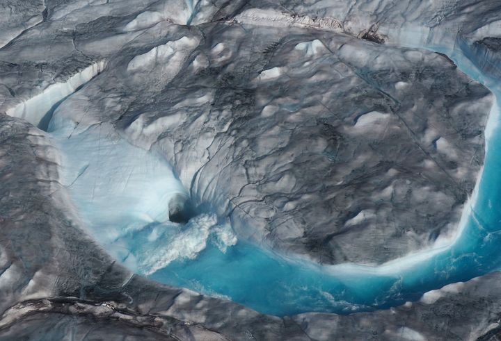 In this image on Aug.1, 2019, large rivers of melting water form on an ice sheet in Greenland and drain through holes into th