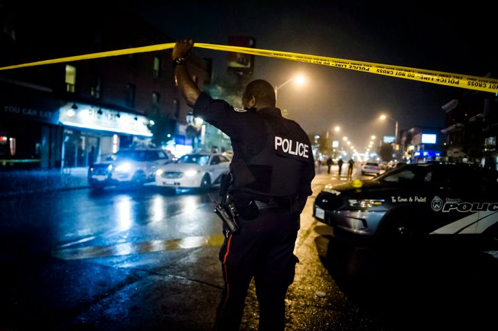 A police officer lifts police tape near the scene of a shooting in Toronto, on July 23, 2018.