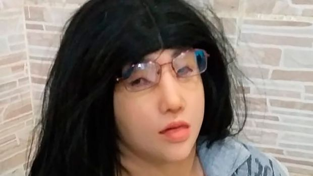 "This photo released by the Rio de Janeiro Penitentiary Administration Secretariat, shows a man who authorities identify as jailed Brazilian drug trafficker Clauvino da Silva, alias ""Baixinho,"" which means ""Shorty,"" wearing a mask, wig, glasses and feminine clothing, as his hands are confined behind his back at a prison complex in Rio de Janeiro, Brazil, Sunday, Aug. 4, 2019. Authorities say the prisoner tried but failed to escape from the prison wearing the disguise. (Rio de Janeiro Penitentiary Administration Secretariat via AP)"