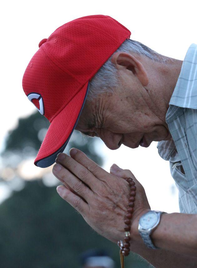広島原爆の日を迎え、原爆死没者慰霊碑の前で手を合わせる男性(広島市中区の平和記念公園)