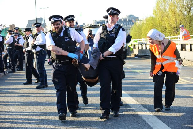 Police officers arrest a climate change protester on Waterloo Bridge in London in April, as a member...