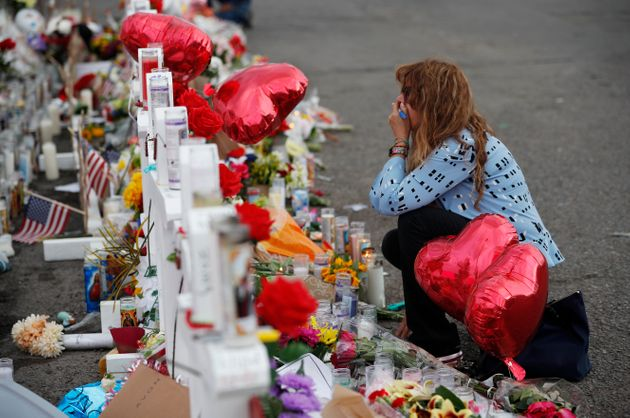 Gloria Garces kneels in front of crosses at a makeshift memorial near the scene of the mass shooting...