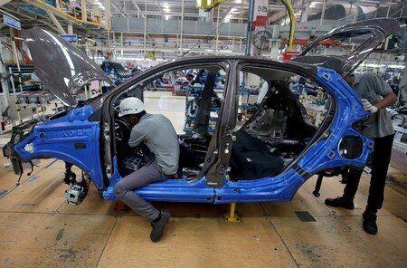 Workers on a car assembly line at the Tata Motors plant in Sanand, on the outskirts of
