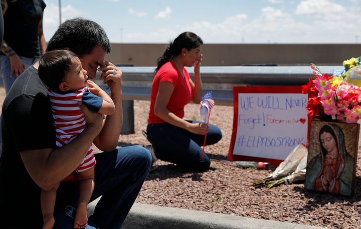 Dr. Julio Novoa, left, and Danielle Novoa, right, kneel beside a makeshift memorial with their 10-month-old son Richard Novoa
