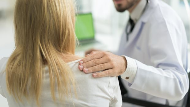 Friendly man doctor hands holding patient arm sitting at the desk for encouragement, empathy, cheering and support while medical examination. Bad news lessening, trust and ethics concept