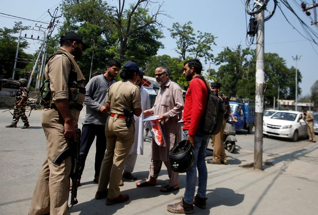A police officer checks papers of people on a road during restrictions in Srinagar August 6,