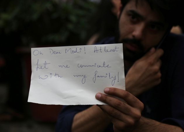 A Kashmiri, who works in Bangalore, holds a piece of paper addressing Prime Minister Narendra Modi during...